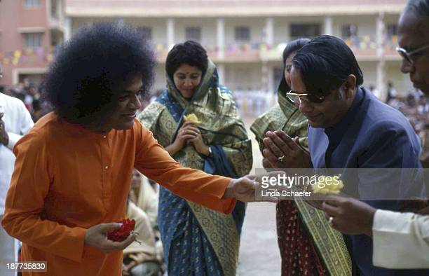 CONTENT] The beloved guru Sathya Sai Baba accepts a yellow rose from a devotee in the temple are of his ashram known as Prasanthi Nilayam in...