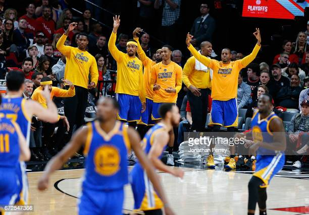 The bench players of the Golden State Warriors celebrate a three point shot by Stepehen Curry against the Portland Trail Blazers during Game Four of...