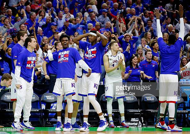 The bench reacts after Wayne Selden Jr #1 of the Kansas Jayhawks dunked against the Connecticut Huskies in the second half during the second round of...