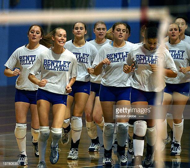 The Bentley College volleyball team is framed by the net as they take a prematch warmup run Included in the shot are Kolleen Ross second from left...