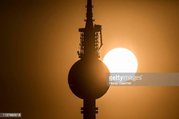 The Berlin tv tower is pictured in front of the setting sun on April 16 2019 in Berlin Germany