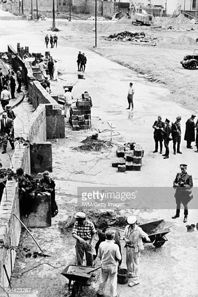 The Berlin Wall 1961 1989 East German construction workers supervised by border guards building the Berlin Wall circa 1961