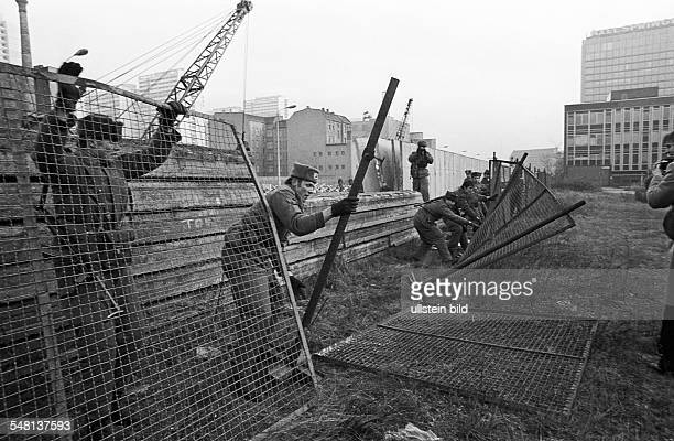 The Berlin Wall East German border guards modernizing a section of the Berlin Wall