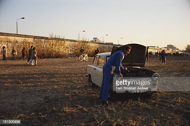 The Berlin Wall seen from East Berlin November 1989 In the foreground a man is working on a Trabant car