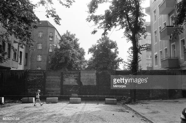 The Berlin Wall the wall running into houses on either side of the road this is East Berlin 6th August 1984