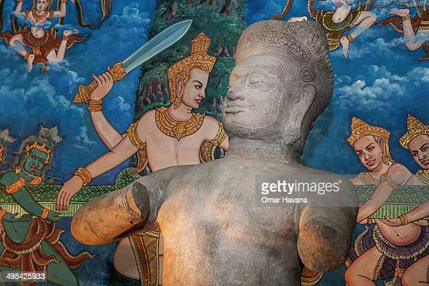 The Bhima statue is displayed in front of a painting representing the Angkor Wat basrelief depicting the churning of the Sea of Milk during a...