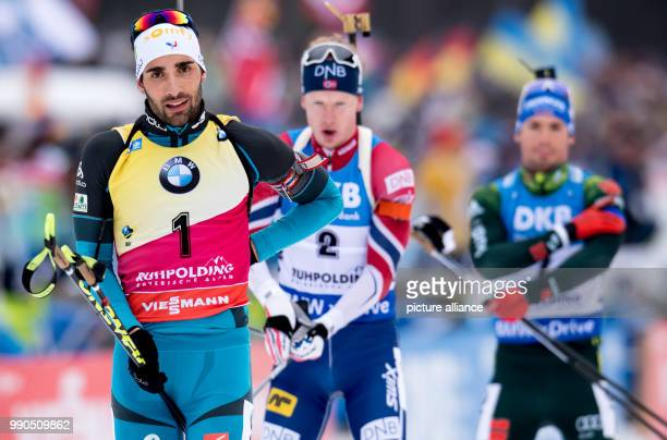 The biathletes Martin Fourcade from France Johannes Thingnes Boe from Norway and Simon Schempp from Germany arrive at the shooting stands during the...