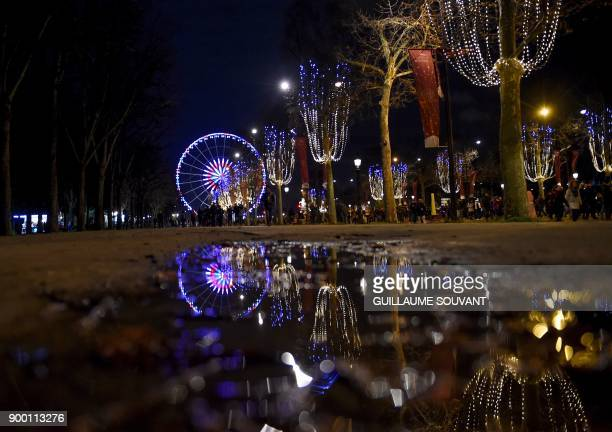 The Big Ferris Wheel of the Place de la Concorde and Christmas decorations are reflected in a pool of water on the ChampsElysees avenue before New...