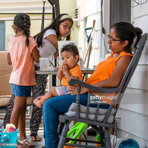 The big happy Latino Mexican-American family resting at the porch of his house