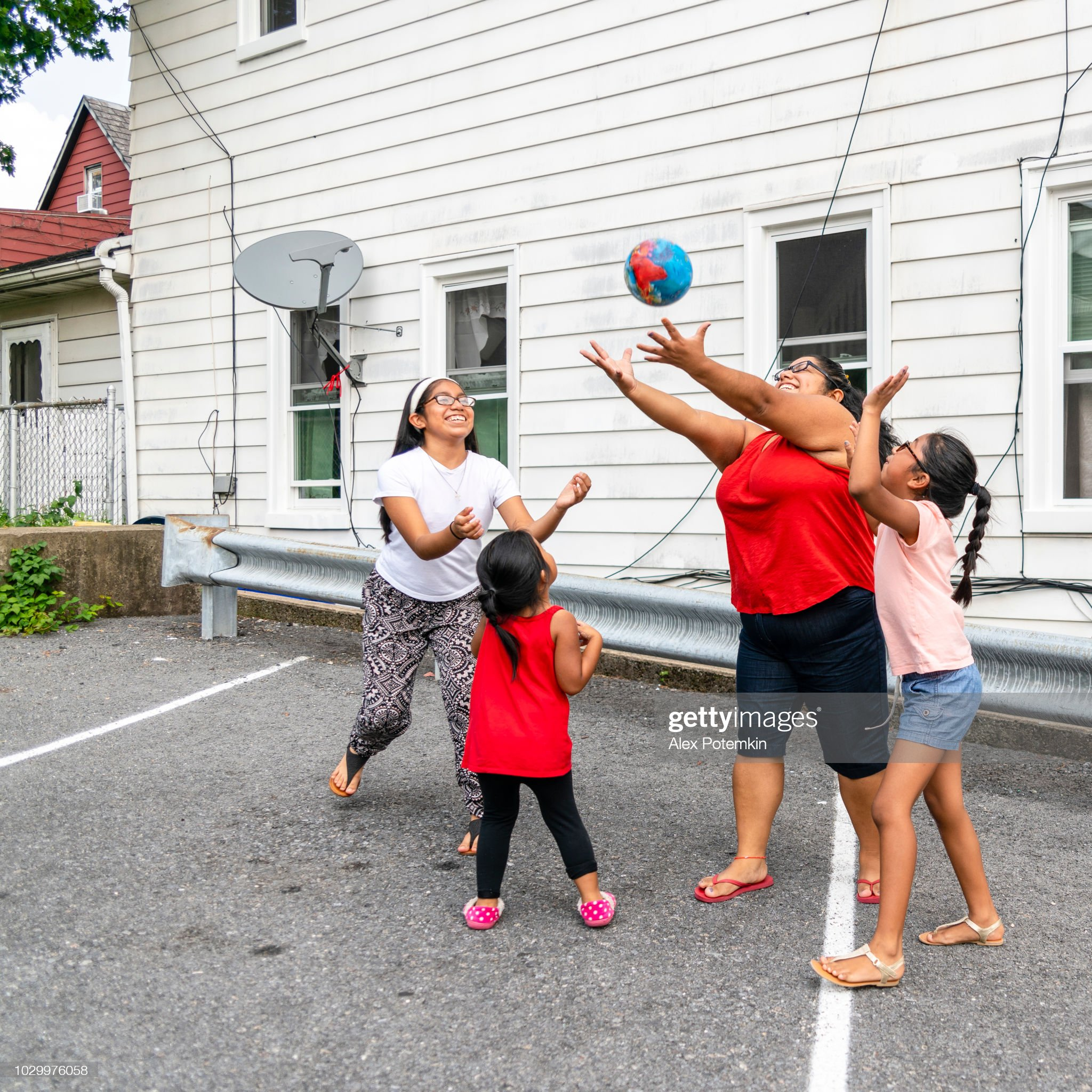 The big happy Latino, Mexican-American family - the mother, body-positive cheerful woman, and kids, girls of different ages - playing with a ball outdoor : Stock Photo
