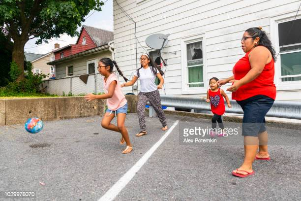 the big happy latino, mexican-american family - the mother, body-positive cheerful woman, and kids, girls of different ages - playing with a ball outdoor - aunt stock pictures, royalty-free photos & images