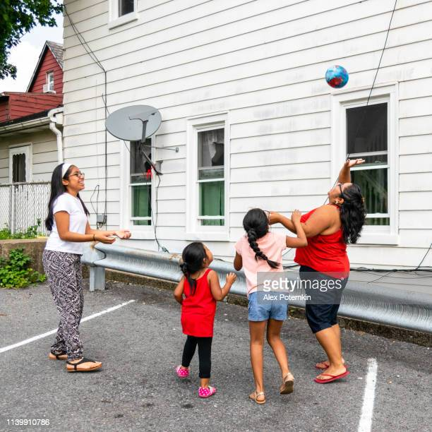 the big happy latino, mexican-american family - the mother, body-positive cheerful woman, and kids, girls of different ages - playing with a ball outdoor - alex potemkin or krakozawr latino fitness stock photos and pictures