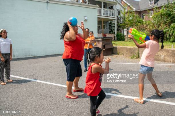 the big happy latino, mexican-american family - the mother, body-positive optimistic smiley woman, her sister, and kids, girls of different ages - playing outdoor with a water gun and having fun - alex potemkin or krakozawr latino fitness stock photos and pictures