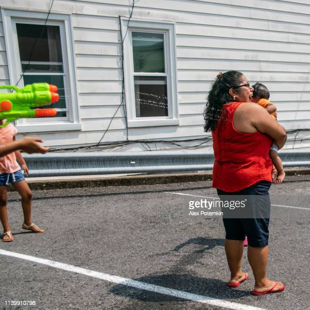 the big happy latino, mexican-american family - the mother, body-positive optimistic smiley woman, and kids, girls of different ages - playing outdoor with a water gun and having fun - alex potemkin or krakozawr latino fitness stock photos and pictures
