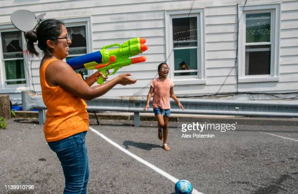 the big happy latino, mexican-american family - the mother, optimistic smiley woman, and kids, girls of different ages - playing outdoor with a water gun and having fun - alex potemkin or krakozawr latino fitness stock photos and pictures