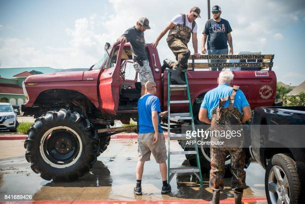 The Big Red Mud Truck rescue team helps flood victims off their truck in Port Arthur Texas September 1 2017 Stormweary residents of Houston and other...