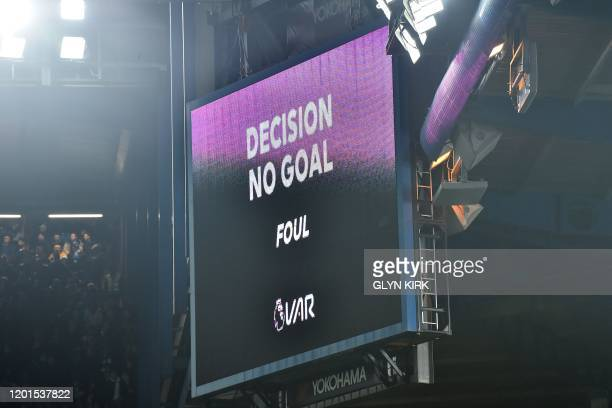 The big screen displays the decision after a VAR review, disallowing a goal from Chelsea's French defender Kurt Zouma for a foul in the build-up...