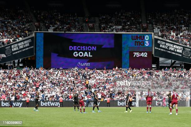 The big screen shows the VAR decision ruling Manchester City's third goal as valid during the English Premier League football match between West Ham...