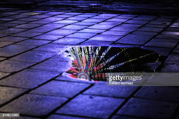 The Big Wheel reflecting into a puddle on Place de La Concorde on February 4 2016 in Paris France