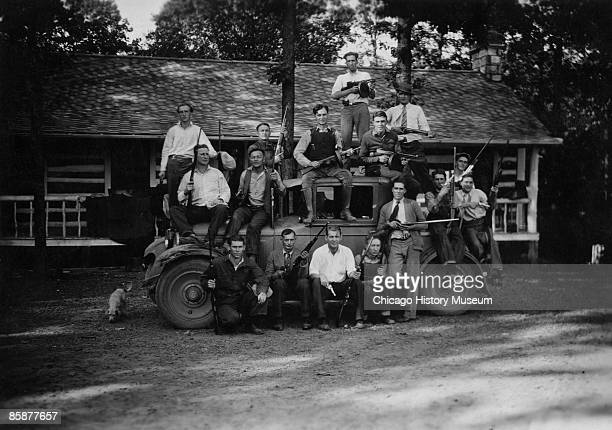 The Birger Gang poses for a group portrait at its hangout Shady Rest in Illinois 1926 Leader Charley Birger is seated atop the driver's door with a...