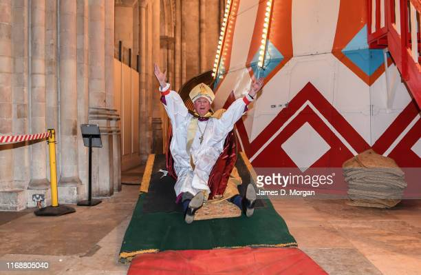 The Bishop of Lynn, the Rt Revd Jonathan Meyrick as he rides the slide of the helter skelter inside the nave of the cathedral on August 18, 2019 in...