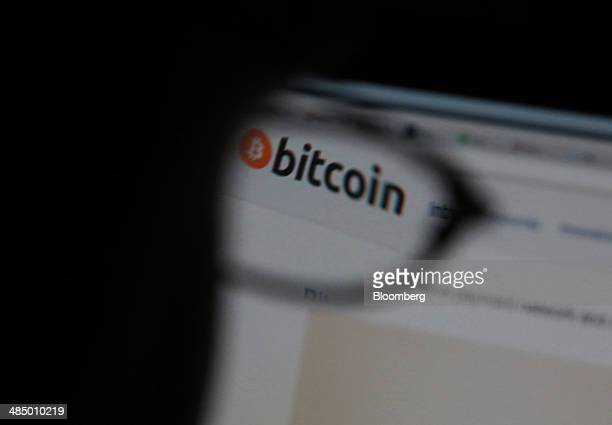 The bitcoin currency logo is seen through the glasses of Alex Wilhelm a bitcoin miner as it is displayed on an internet website on his computer...