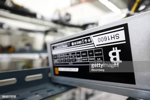 The bitcoin logo is displayed on a power supply unit at a cryptocurrency mining facility in Incheon South Korea on Friday Dec 15 2017 Hedge funds are...