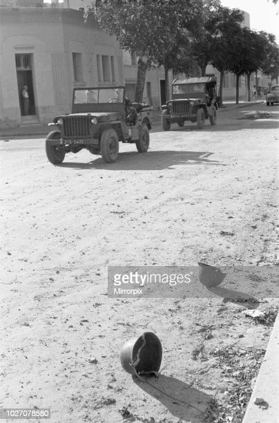 The Bizerte Crisis 1961 Discarded helmets of the retreating Tunsian army lay in the road as patrolling French paratroopers drive through the streets....