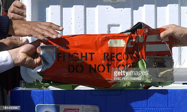 The black box of the Flash Airlines flight is removed from an ice box 17 January 2004 on the military port of Sharm el Sheikh One of the two black...