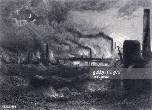 'The Black Country' near Bilston Staffordshire showing a scene of heavy industry at night with smoking chimneys fire from gas outlets and hot coals...