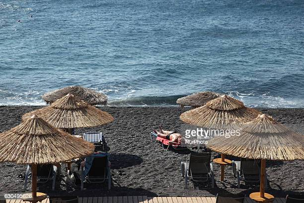 The black pebble Kamari beach is a popular tourist destination in the small Village of Kamari on Santorini Island, Greece on 4 July 2016.