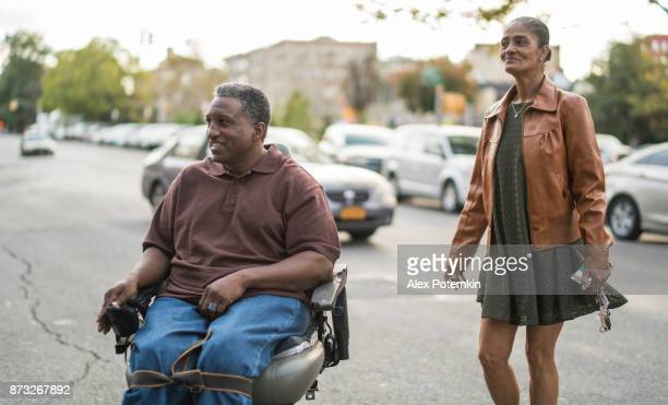 the black senior disabled veteran in wheelchair and his wife crossing the street in bronx - african american man helping elderly stock pictures, royalty-free photos & images