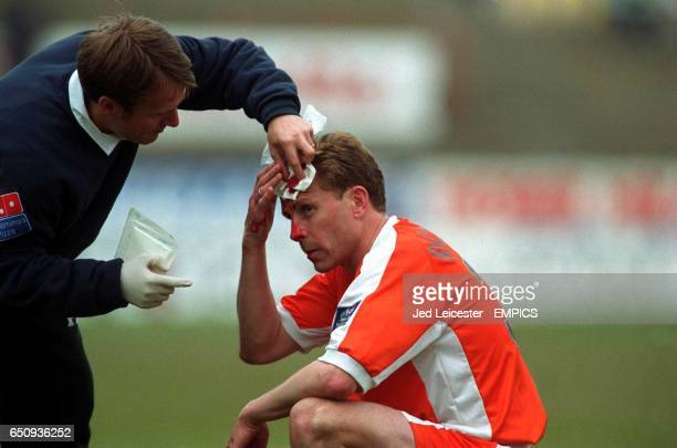 The Blackpool physio tries to mop up the blood streaming from a wound on Kevin Richardson's forehead