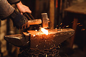 The blacksmith manually forging the red-hot metal on the anvil in smithy with spark fireworks.