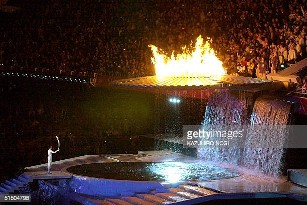 The blazing cauldron slowly ascends a ramp leading to its final position high above the Olympic Stadium 15 September, 2000 in Sydney after...