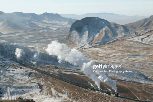 The bleak winter landscape of the Jing Peng pass provides a fine backdrop to a doubleheaded coal train emerging from tunnel No 4 and leaving wraiths...