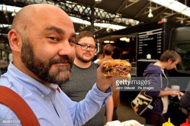 The Bleecker Street burger van at Spitalfields market in east London where a customer tries its award winning burger the Bleecher Black which is a...