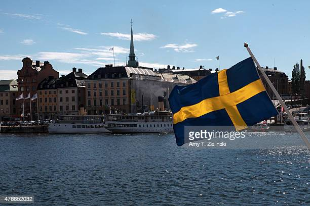 The blue and yellow flag of Sweden waves across from architecture on Stadsholmen in Gamla stan days before the Royal Wedding of Swedish Prince Carl...