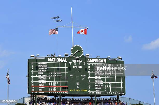 The Blue Angels fly behind the scoreboard at Wrigley Field during the fifth inning of a game between the Chicago Cubs and the Toronto Blue Jays on...