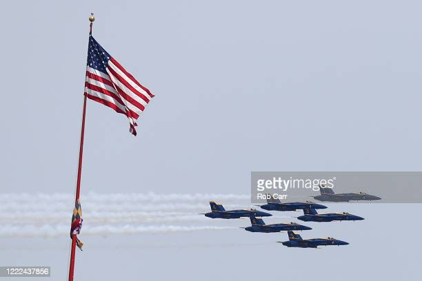 The Blue Angels fly past an American flag on May 02 2020 in Baltimore Maryland The Blue Angels and Thunderbirds took to the sky to pay tribute to the...