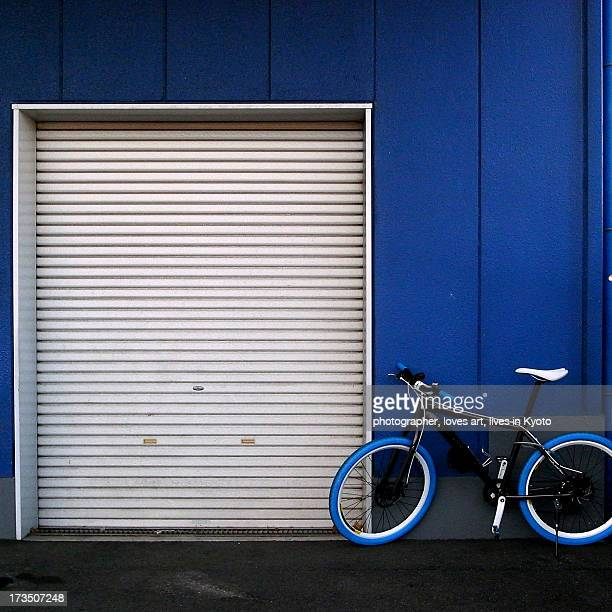 The blue bicycle in front of a blue warehouse.