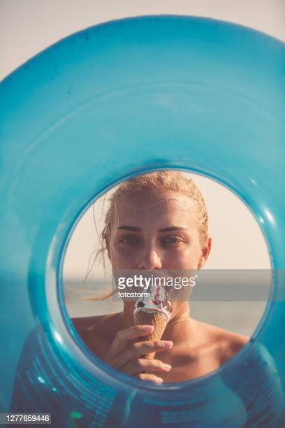 the blue circle of a swimming float with a woman eating ice cream - active lifestyle stock pictures, royalty-free photos & images