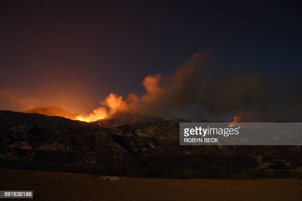 The Blue Cut Fire burns after sunset in the mountains near Wrightwood California August 17 in this slow shutter speed exposure photo / AFP / Robyn...