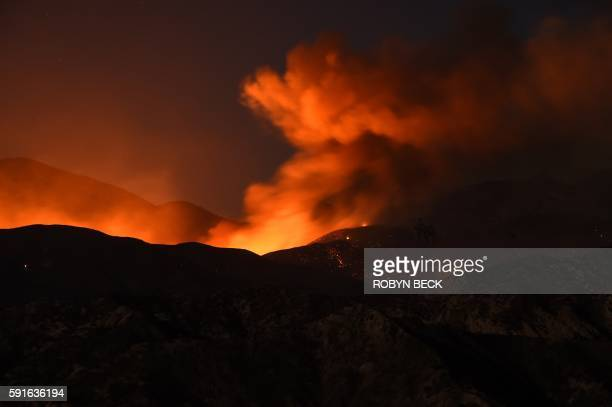 TOPSHOT The Blue Cut Fire burns after sunset in the mountains near Wrightwood California August 17 in this slow shutter speed exposure photo / AFP /...