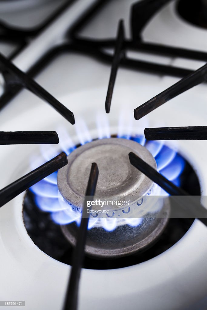 The blue flame of a lit gas stove burner, close-up : Stock Photo