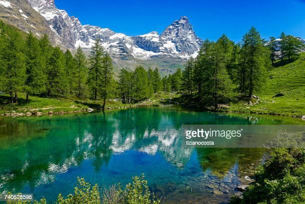 the blue lake and the matterhorn, val daosta, italy - monte cervino foto e immagini stock