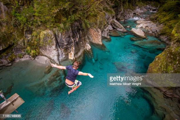 the blue pools of makarora offer enticing blue waters to swim in. a man jumps off a bridge into the water. - lagoon stock pictures, royalty-free photos & images