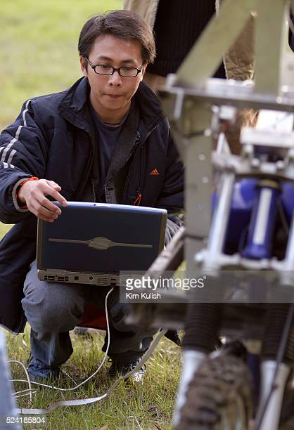 The Blue Team member Sing Yiu Cheung reloads software into the vehicle during a test of their robotic motorcyle in preparation of the DARPA Grand...