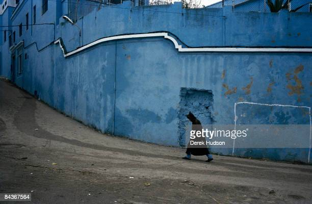 The blue wall of the Darna Center For Girls a hospice in the Marshan district of Tangier A man in a traditional winter jalaba walks up the steep road...
