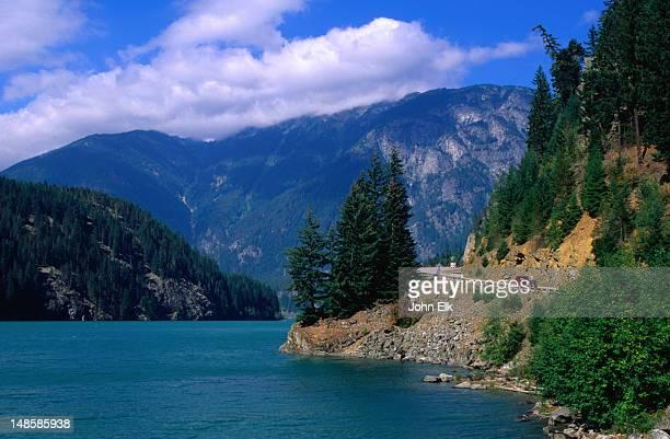 the blue-green waters of diablo lake carry trout and the shoreline provides stunning scenery. - diablo lake - fotografias e filmes do acervo